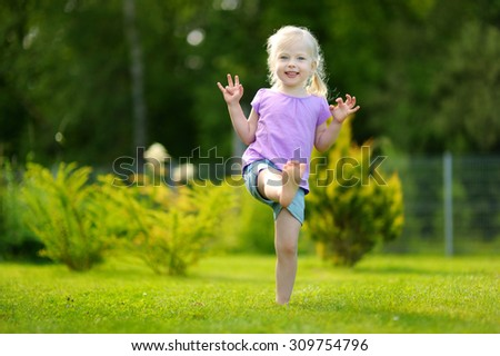 Funny little girl having fun outdoors on warm and sunny summer day - stock photo