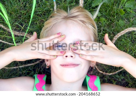 Funny little girl hiding her face with her hands - stock photo