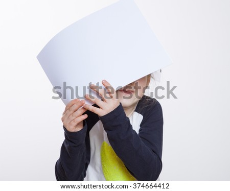 Funny little girl holding above her head sheet of paper, neutral background
