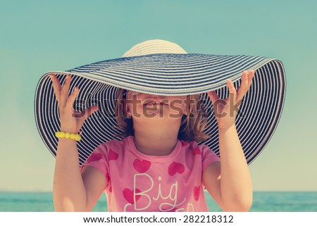 Funny little girl in a big striped hat on the beach. The image is tinted. - stock photo