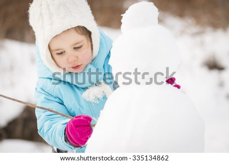 Funny little girl  in a warm winter outfit, building a snow man. Kid playing outdoors in winter. Happy little kid is playing in snow, good winter weather. Child building snowman. - stock photo