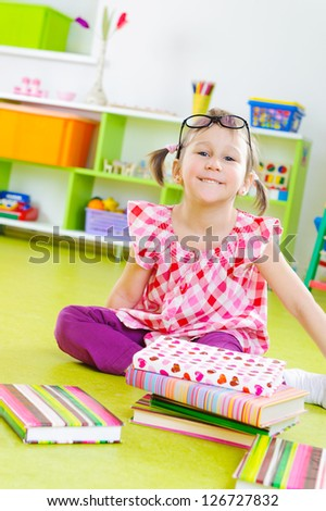 Funny little girl in glasses with books on floor