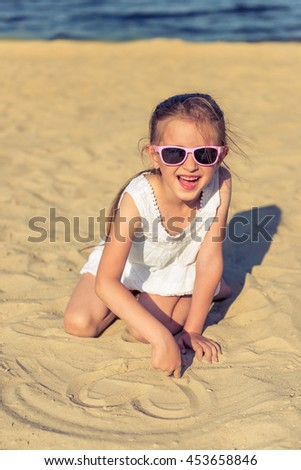 Funny little girl in sun glasses is looking at camera and smiling while playing on the sunny seaside - stock photo