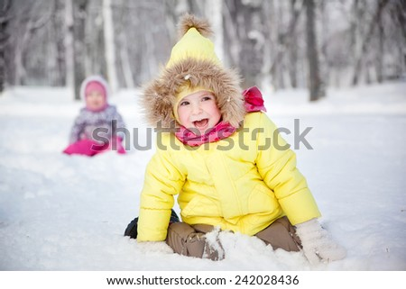 funny little girl in winter clothes in a snowy forest - stock photo