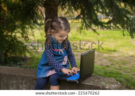 Funny little girl learning with tablet pc in the park, outdoor