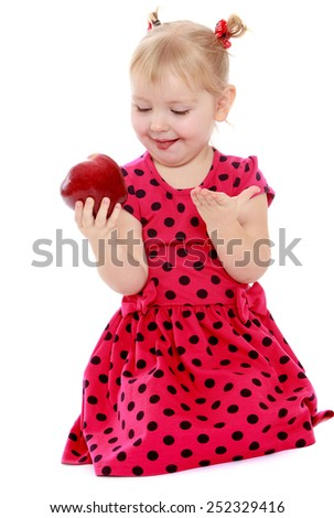 Funny little girl looks at a delicious red apple.Isolated on white background, Lotus Children's Center.