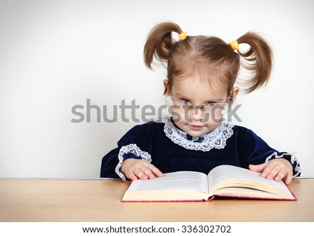 Funny little girl reading book