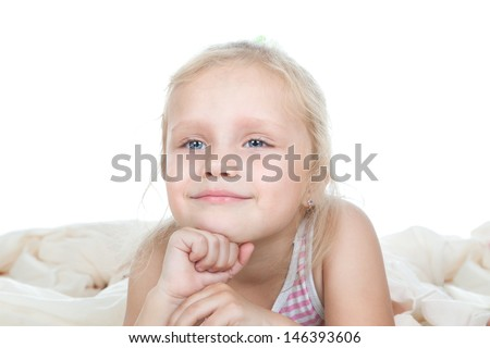 Funny little girl relaxing on a bed over white