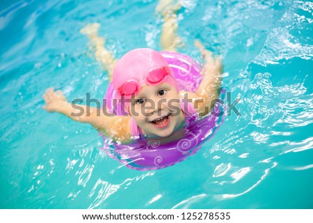 Funny little girl swims in a pool in an pink life preserver