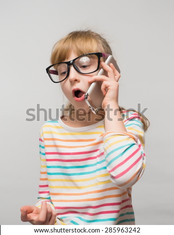 Funny little girl talking on a cell phone - stock photo