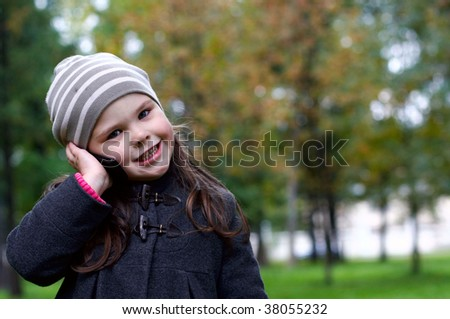 Funny little girl talking to a cell phone at beautiful autumn day