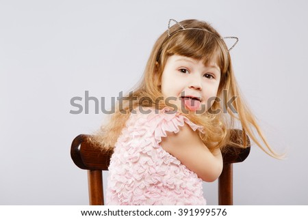 Funny little girl wearing pink dress and metal cat ears sitting in chair and showing tongue, looking at camera, gray studio background, copy space. - stock photo