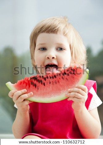 Funny little girl with big slice of watermelon