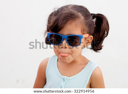 Funny little girl with pigtails and sunglasses outdoor - stock photo