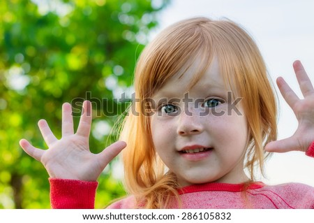 funny little girl with red hair and big eyes with your hands - stock photo