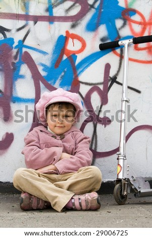 Funny little girl with scooter is sitting on the ground near graffiti painted wall - stock photo
