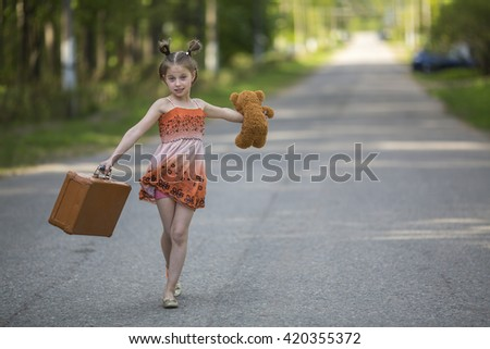 Funny little girl with suitcase and Teddy bear walking is on the road. - stock photo