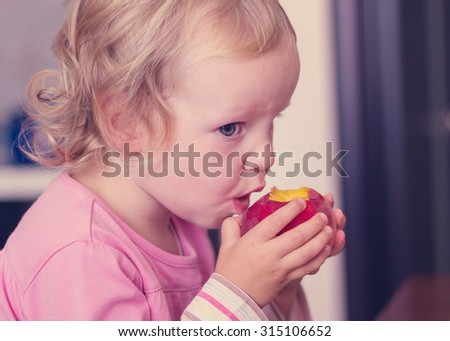 Funny little girl (2 years) eat a peach. Selective focus. - stock photo