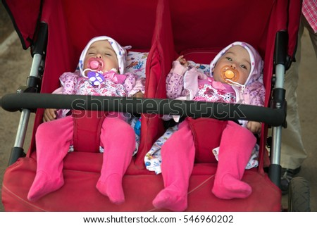 Funny little girls twins in double stroller, close up portrait