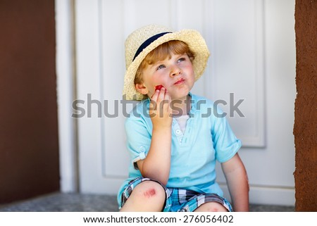 Funny little kid boy eating fresh organic strawberries in domestic garden, on warm summer sunny day. - stock photo