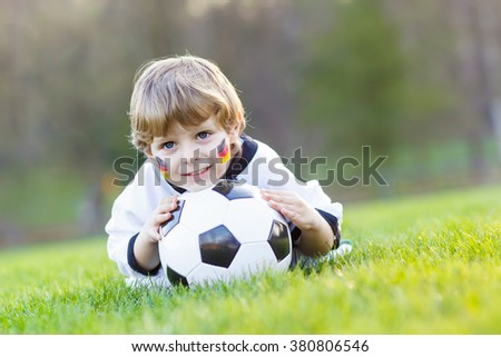 Funny little kid boy  having fun with playing soccer with football on field, outdoors. In white German national uniform and painted  flag on face. Happy child about european championship - stock photo