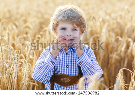 Funny little kid boy in traditional German bavarian clothes, leather shorts and check shirt, walking happily through wheat field near  hay stack or bale. Active leisure with children on summer day. - stock photo