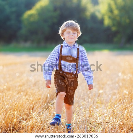 Funny little kid boy in traditional German bavarian clothes, leather shorts and check shirt, walking happily through wheat field near  hay stack or bale. Active outdoors leisure with children - stock photo