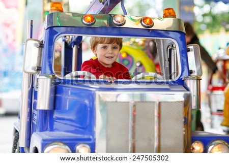 Funny little kid boy riding on a merry-go-round carousel, smiling and having fun at a funfair or amusement park. Active family leisure with kids. - stock photo