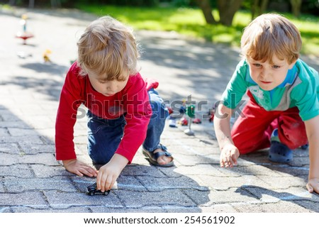 Funny little kid boys, twins, playing together with car toys in summer garden. Active outdoors leisure for children on hot summer sunny day. Family lifestyle - stock photo