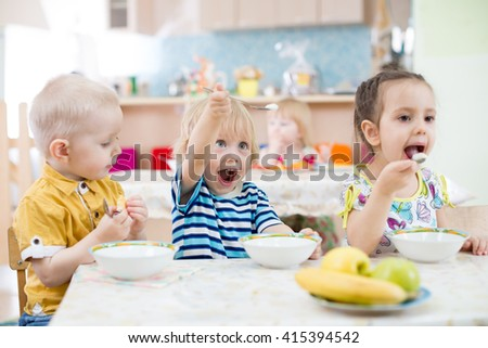 Funny little kid playing and eating in kindergarten - stock photo