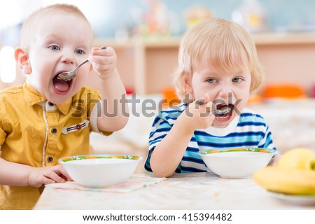 Funny little kids eating from plates in kindergarten - stock photo