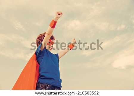 Funny little power super hero child (boy) in a red raincoat. Superhero concept. Instagram colors toning - stock photo