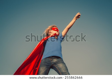 Funny little power super hero child (girl) in a red raincoat. Superhero concept. Instagram colors toning - stock photo