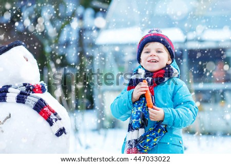 Funny little toddler boy making a snowman and eating carrot, playing and having fun with snow, outdoors  on cold day. Active outdoors leisure with kids in winter. - stock photo