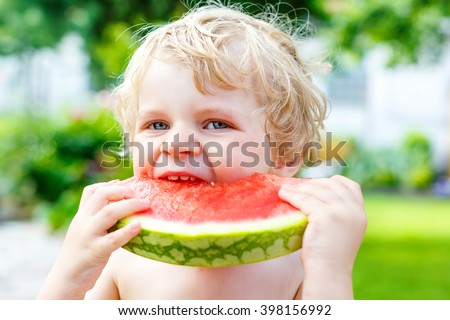 Funny little toddler boy with blond hairs eating watermelon in outdoor kindergarden. Kid tasting healthy snack. Healthy food for children. - stock photo