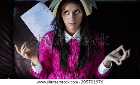 Funny looking brunette woman student trying to study in her room. Funny process of studying for exams