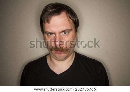 funny looking guy is not impressed with what he is looking at - stock photo