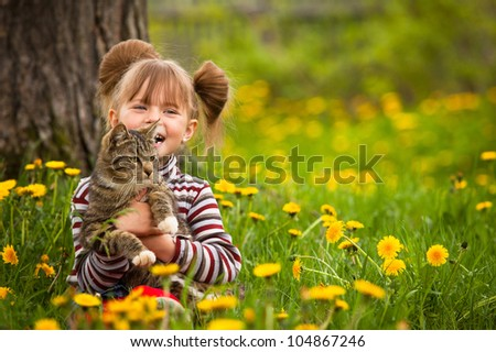 Funny lovely little girl playing with a cat - stock photo
