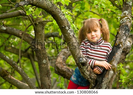 Funny lovely little girl posing sitting on a tree in the garden. - stock photo