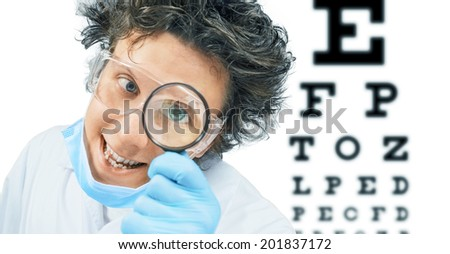 Funny man doctor ophthalmologist looks through a magnifying glass on a background of eyesight test chart, healthcare - stock photo