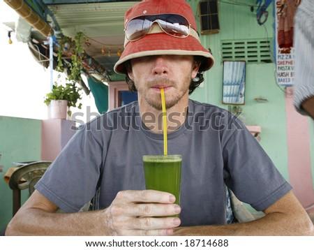 Funny man drinking fresh mint and lemon juice - stock photo