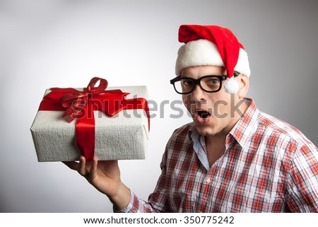 Funny man in a hat Santa with a Christmas present in his hand. A man holding a box with a red ribbon - stock photo