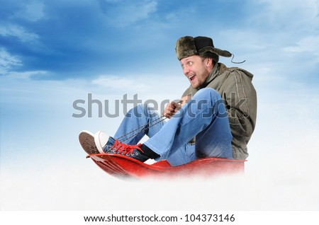 Funny man in earflaps, on a sled in the snow, concept winter driving - stock photo