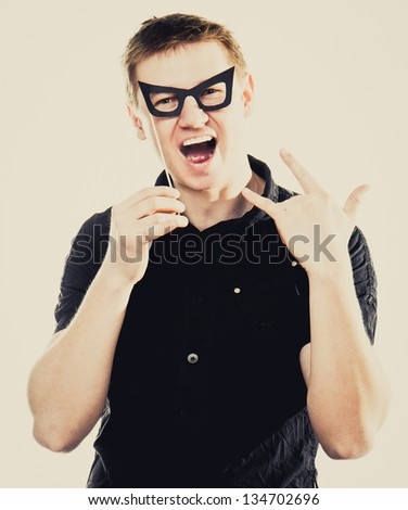 funny man in fake glasses with Rock and roll sign - stock photo