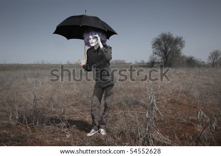 Funny man in the steppe holding umbrella and looking beyond the horizon. Artistic darkness and colors added - stock photo