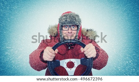 Funny man in winter clothes with steering wheel, snow blizzard. Concept car driver