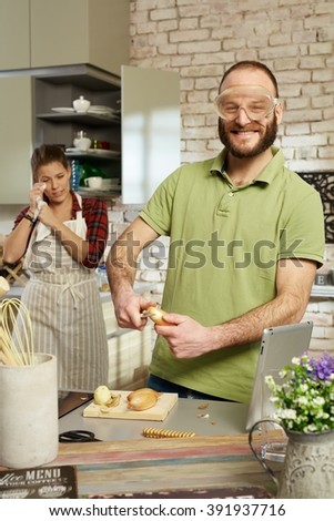 Funny man peeling onion in protective eyewear in kitchen.