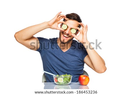 funny man playing with cucumber on eyes, havind healthy food in front - stock photo
