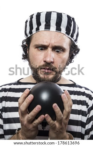 Funny man prisoner criminal with chain ball and handcuffs in studio isolated on white background - stock photo