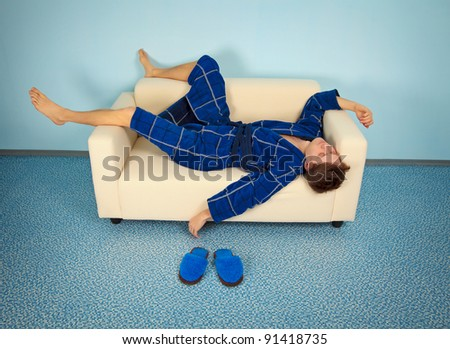 Funny man resting at home on the couch - stock photo